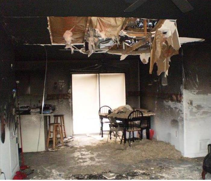 fire damaged kitchen, debris hanging from the ceiling, a mess
