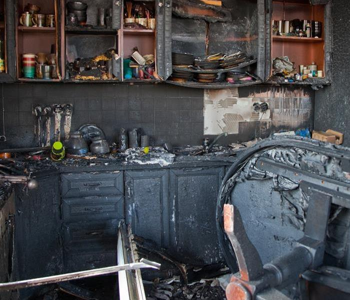 A kitchen with fire, smoke, and soot damage.