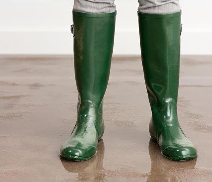 A person standing in green rain boots.