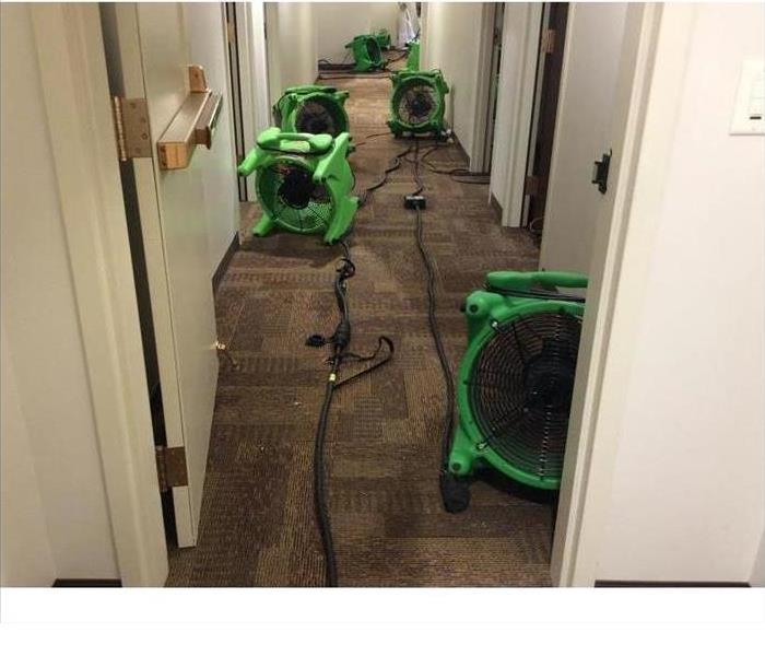 High-velocity axial fans placed on the carpet of a building drying water damage