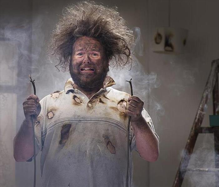 A guy holding electrical wires with fried hair and soot on his face.